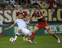 Falling US midfielder Clint Dempsey (8) plays the ball despite being knocked down by Poland defender Dariusz Pietrasiak. The U.S. Men's National Team tied Poland 2-2 at Soldier Field in Chicago, IL on October 9, 2010.