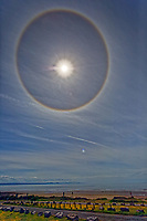 Pictured: A sun halo is seen in the sky above Rest Bay near Porthcawl, south Wales, UK. Thursday 27 May 2021<br /> Re: This weather phenomenon is not uncommon, but cool to see and is called a halo. It is caused by high thin cirrus clouds about 20,000 ft in the sky. They can be very faint that it still looks mostly sunny! This type of cloud is made up of millions of very tiny, ice crystals. When the sun shines through it at just the right angle, the light splits or refracts and reflects and creates a perfect 22-degree circle or halo.