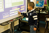 MR / Schenectady, NY. Zoller Elementary School (urban public school). Kindergarten inclusion classroom. Student (boy, 5, African-American) selects day of the week using his finger on digital whiteboard at calendar time. This is part of a daily routine to help reinforce basic concepts about time by frequent repetition. MR: Ste14. ID: AM-gKw. © Ellen B. Senisi.