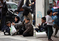 Pictured: Afghan widow and mother of five Karima, 35 (2nd L) with three of her children L-R Samar, 5 and Fahad, 7 and Saud, 9 eat at a street corner Tuesday 08 March 2016<br /> Re: Migrants at Victoria Square, in central Athens, Greece.