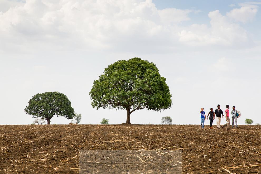 A group of young men walk across barren farmland near the city of Latur.