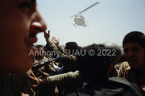"""Tehran, Iran .June 6, 1989..Mourners at the burial site for the Grand Ayatullah Sayid Ruhullah Musawi Khomeini at the Beheht-E-Zahra cemetery. His body is flown to this site in by this helicopter but frenzied crowds prevent the first attempt to bury him. Late in the day, after some of the crowds were cleared, he is buried at this site.He died of heart attack on June 3, 1989...Khomeini was a senior Muslim cleric, Islamic philosopher and marja (religious authority), and the political leader of the 1979 Iranian Revolution that saw the overthrow of Mohammad Reza Pahlavi, the last Shah of Iran. Following the revolution, Khomeini became the country's Supreme Leader?the paramount political figure of the new Islamic Republic...Khomeini was a marja al-taqlid, (source of imitation) and important spiritual leader to many Shia Muslims. He was also an innovative Islamic political theorist, most noted for his development of the theory of velayat-e faqih, the """"guardianship of the jurisconsult (clerical authority)"""". He was named Time's Man of the Year in 1979 and also one of Time magazine's 100 most influential people of the 20th century."""