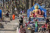 "Nepal, Kathmandu, Swayambhunath.  Buddha Statues Flank the Stairs Leading to the Stupa at the top of the Hill.  The Buddha is Demonstrating the ""Earth is my Witness"" Gesture.  (Bhumisparsha Mudra)."