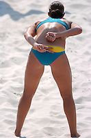 A female beach volleyball player gives hand signals on the beach during a match.