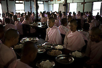 Nuns pray before eating lunch at a monastery in Mandalay. Buddhist nuns are not treated with the same reverence as their male counterparts, having to prepare their own food, and living in monasteries that are often pushed to the outskirts of town. The monasteries themselves are usually less well kept than the monks' monasteries due to a lack of funds..