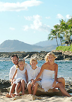 Family portrait with mom, dad and two kids on the beach while on vacation in Hawaii