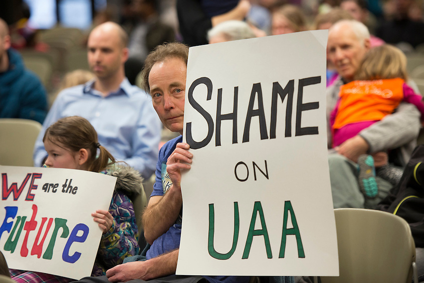 Ken Baitsholts and his daughter hold signs protesting the planned eviction of Tanaina Child Development Center as UAA Chancellor Tom Case and his cabinet members hold a prioritization open forum in the student union. The center, which has been on campus since 1979, received an eviction notice from UAA on January 28th and has until May 8th to relocate. Photo by James R. Evans /  The Northern Light