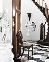 An antique torso is displayed on a Perspex plinth in the staircase hall