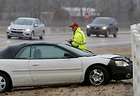 Rob Clements, with Ed's Towing, collects information Wednesday, February 10, 2021, from a vehicle sitting perpendicular to Garland Avenue near the Pauline Whitaker Animal Science Center in Fayetteville. Multiple accidents occurred Tuesday night into Wednesday morning in northwest Arkansas including a two vehicle crash on the Illinois bridge on Arkansas 16 in Benton County where two people were killed as hazardous road conditions settled over the area. Check out nwaonline.com/210211Daily/ and nwadg.com/photos for a photo gallery.<br /> (NWA Democrat-Gazette/David Gottschalk)
