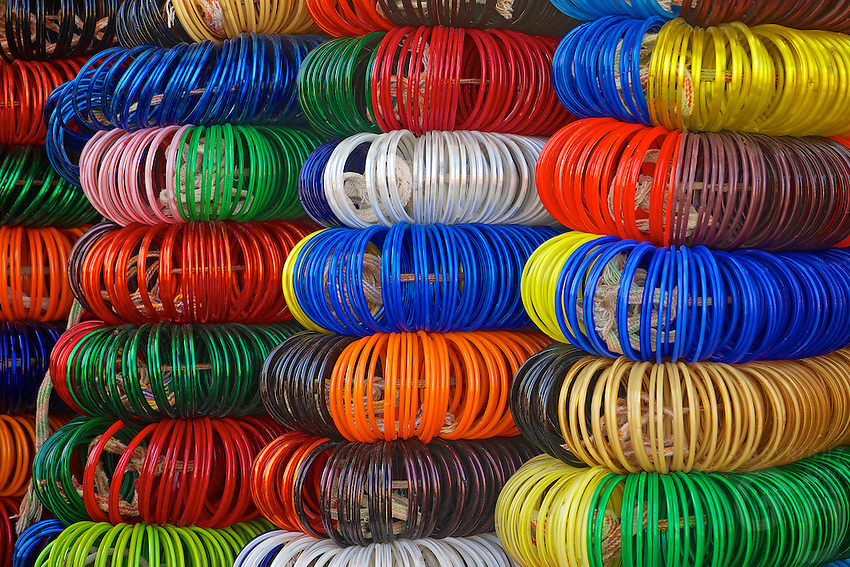 "Bangles for sale in Jodhpur Rajasthan India. The city is known as the ""Sun City"" for the bright, sunny weather it enjoys all the year round. It is also referred to as the ""Blue City"" due to the vivid blue-painted houses around the Mehrangarh Fort. The old city circles the fort and is bounded by a wall with several gates."