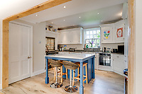 BNPS.co.uk (01202 558833)<br /> Pic: Mullucks/BNPS<br /> <br /> Pictured: Kitchen with breakfast bar. <br /> <br /> Time for a change...<br /> <br /> A former granary with an impressive clock tower on top is on the market for £1.45m.<br /> <br /> The new owners of the aptly-named The Clockhouse will have a tall order adjusting this timepiece when the clocks go back at the end of October.<br /> <br /> The Grade II listed property has a 10ft central wooden clock tower which is believed to date back to the construction of the original granary building in the Georgian era.