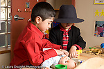 Education Preschool 3-5 year olds dressup pretend play two boys playing with doll one wearing hat and jacket horizontal