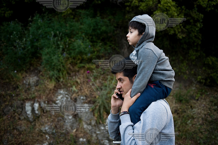 An Afghan man carryies his child while walking the the 9 hour distance from Skala Sykaminias to the village of Moria on the island of Lesbos where the First Reception Centre for refugees is located. Every day hundreds of refugees, mainly from Syria and Afghanistan, are crossing in small overcrowded inflatable boats the 6 mile channel from the Turkish coast to the island of Lesbos in Greece.