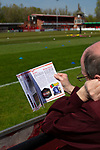 A spectator reading the match programme before Ilkeston Town host Walsall Wood in a Midland Football League premier division match at the New Manor Ground, Ilkeston. The home team were formed in 2017 taking the place of Ilkeston FC which had been wound up earlier that year. Watched by a crowd of 1587, their highest of the season, the match was top versus second, however, the visitors won 4-0 and replaced their hosts at the top of the division on goal difference with two matches to play