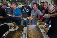 Switzerland. Canton Ticino. Bellinzona. Lunch time. Pasta  with bolognese sauce. The wave of national protest in the construction industry began on October 15 in Ticino. 3000 masons from Ticino interrupted their work to meet in Bellinzona and demand that retirement be maintained at 60. In addition to retirement at 60, the fight against wage dumping and longer working hours are at the heart of the demands. Unia and OCST unions said in a joint statement that masons have had enough after a year of blocking negotiations and blackmail. The workers and their unions have therefore decided to start a national protest. If no agreements are found between workers and constructions companies, a strike might occur in the near future. 15.10.2018 © 2018 Didier Ruef