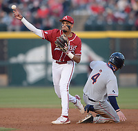 Arkansas shortstop Jalen Battles makes the late relay throw to first Friday, April 2, 2021, after forcing out Auburn third baseman Rankin Woley during the third inning of play at Baum-Walker Stadium in Fayetteville. Visit nwaonline.com/210403Daily/ for today's photo gallery. <br /> (NWA Democrat-Gazette/Andy Shupe)