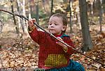 2 year old toddler girl outside: exploring: sitting on rock, examining stick