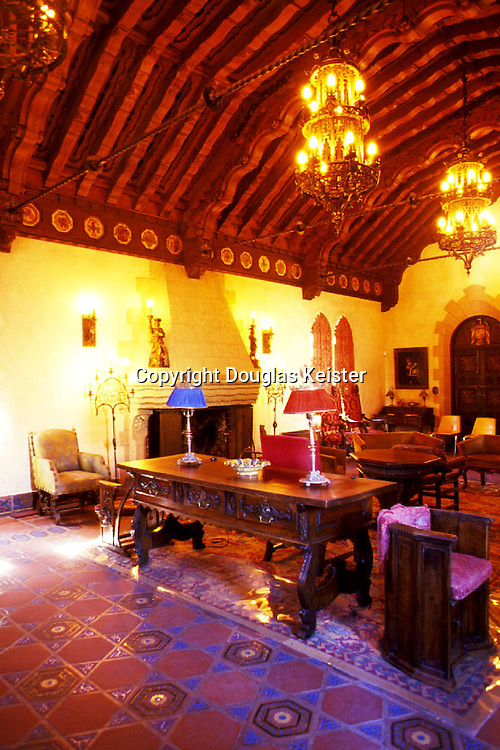 Scotty's Castle<br />Death Valley California<br />The upper music room, with its elaborate carved redwood ceiling beams set off by massive double-staged chandeliers, typifies the quality of detail found throughout the Castle.  The clay tile floor is laid in arabesque pattern harking from Moorish Spain; despite its seeming complexity, its tiles consist only of triangles and hexagons.  The row of tile medallions in the frieze are thought to be the coats of arms of towns from which the Castle's European craftsmen originated.