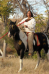 A Native American Indian man sitting on a war painted horse portrait