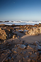 Long shadows, a rocky beach, Pacific waves and a gibbous moon at Pescadero State Beach.