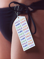 Close up of a ticketwith the words sale on it attached to a black bikini being worn by a women