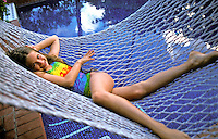 A girl in a bathsuit smiles as she lounges in a hammock above a swimming pool on Oahu.