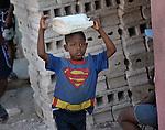 A boy carries water on his head as he walks along a street in Port-au-Prince, Haiti.