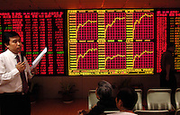 A stock analyst analyzes market to investors at the end of the exchange day in a stock exchange of Beijing. China's bullish stock market shrugged off the central bank's most aggressive monetary tightening this year, hitting a fresh all-time high as individual investors poured money into shares..21 May 2007