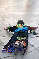 Tibetan Buddhist woman prostrating on the Barkhor pilgrim circuit around the Jokhang Temple, Lhasa, Tibet.