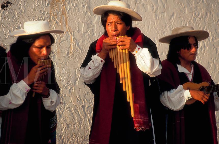Men playing Otavalan folk music; one playing the pan flute. Ecuador.