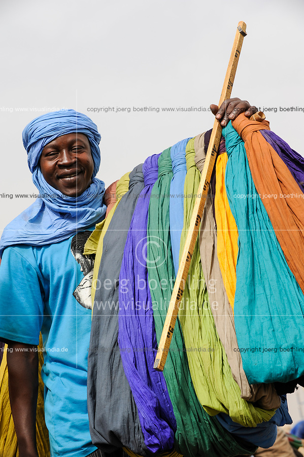 MALI Mopti, street hawker sells coloured cloth for use as shesh or Tagelmust, the turban of Touareg, Haussa and Songhai