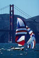 A sailboat sails downwind from the Golden Gate Bridge with full red, white and blue spinnaker sails. San Francisco, California.