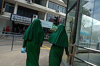 Two women walking downtown wearing the traditional Islamic dress, Male, Maldives.