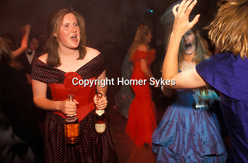 Cirencester, Gloucestershire. 1995 <br /> With two bottle of pink champagne in hand and a complexion and dress to match, a student Sloane Ranger gives it all she's got on the disco dance floor at the Royal Agricultural College annual end of year dance.