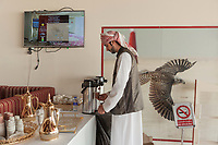 "United Arab Emirates (UAE). Abu Dhabi. Organised jointly by the Hamdan Bin Mohammed Heritage Center (HHC) and Abu Dhabi Falconers Club, the UAE Falconers League has a total of nine rounds that run until February 19 between Dubai and Abu Dhabi. A waiter wearing a white thobe is filling a cup of tea. A thawb (thobe, dishdasha, kandora) is an ankle-length garment, usually with long sleeves, similar to a robe, kaftan or tunic, commonly worn in the Arabian Peninsula. The headdress is called ghutrah. On the wall, a picture of a Peregrine falcon flying at full speed during a competition. Falcons are birds of prey in the genus Falco, which includes about 40 species. Adult falcons have thin, tapered wings, which enable them to fly at high speed and change direction rapidly. Falcons kill with their beaks, using a ""tooth"" on the side of their beaks. A no smoking sign written in arabic and english languages forbids people to smoke indoors. The United Arab Emirates (UAE) is a country in Western Asia at the northeast end of the Arabian Peninsula. 18.02.2020  © 2020 Didier Ruef"