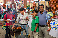 Tlacolula, Oaxaca; Mexico.  Tlacolula's Covered Indoor Meat Market consists of many individual stalls.  In the middle of the corridor are small barbecue grills where buyers such as this family can cook their own purchase.