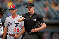 Umpire Thomas Roche during the lineup exchange with Rouglas Odor (left) and Sean Williams (22) before an Eastern League game between the Reading Fightin Phils and Akron RubberDucks on June 4, 2019 at Canal Park in Akron, Ohio.  Akron defeated Reading 8-5.  (Mike Janes/Four Seam Images)