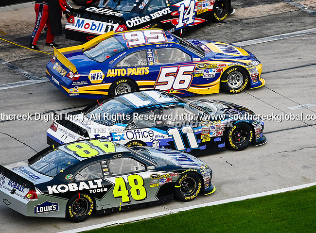 Martin Truex Jr., driver of the (56) NAPA Auto Parts Toyota, Denny Hamlin, driver of the (11) FedEx Office/March of Dimes Toyota, and Jimmie Johnson, driver of the (48) Lowe's/Kobalt Tools Chevrolet, all leave pit row during the Samsung Mobile 500 Sprint Cup race at Texas Motor Speedway in Fort Worth,Texas.