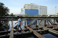 An Indonesia man walks across a flooded bridge in central Jakarta.