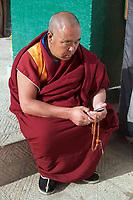 A Tibetan monk checks his cellphone in the Upper Wutan Monastery, Rebgong (Chinese name - Tongren),  on the Qinghai-Tibetan Plateau. China.