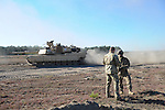 "(L-r) Danish Captain Ulrik Sorensen of the First Armored Battalion speaks with American Captain Erik Hamilton, Commander of Delta Company, 2nd Battalion, 7th Infantry Regiment, 1st Armored Brigade Combat Team, 3rd Infantry Division as an American M1A2 Abrams tank passes during a tank maneuver training exercise where Americans and Danes worked together to simulate battle against opposing forces at the Drawsko Pomorskie Training Area in Poland on June 11, 2015.  NATO is engaged in a multilateral training exercise ""Saber Strike,"" the first time Poland has hosted such war games, involving the militaries of Canada, Denmark, Germany, Poland, and the United States."