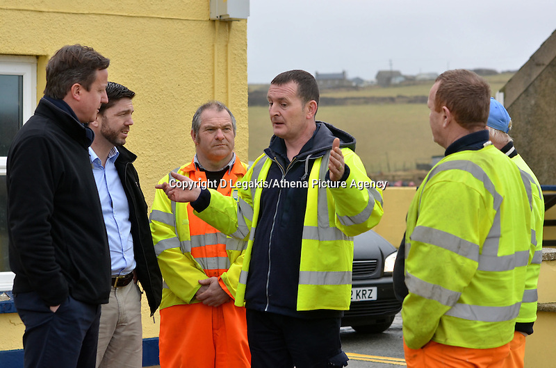 Pictured: Prime Minister David Cameron (L) speaks to Pembrokeshire Council workers who have been working to rectify the damage caused in Newgale, Pembrokeshire. Wednesday 19 February 2014<br /> Re: Prime Minister David Cameron has today visited the Pembrokeshire village of Newgale which suffered severe damage during the early January and February storms.