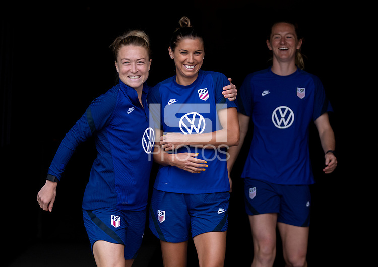 HOUSTON, TX - JUNE 9: Emily Sonnett #14 and Alex Morgan #13 of the USWNT walk onto the field before a training session at BBVA Stadium on June 9, 2021 in Houston, Texas.