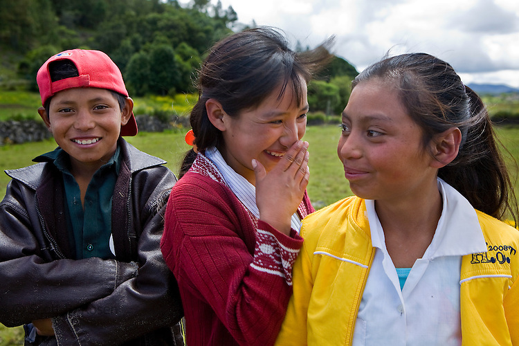 Three smiling Guatemalan children pose near their church in San Nicolas, Ixil, Western Highlands, Guatemala