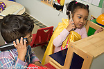 Preschool 2-3 year olds boy and girl pretend play talking on telephones