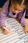 Preschool classroom New York City 4 year old class girl signing in on daily name chart learning to write letters of her name vertical Hispanic American