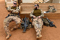 MALI, Gao, Minusma UN peace keeping mission, Camp Castor, german army Bundeswehr, two soldier in desert camouflage uniform take a break, HK Heckler and Koch machine gun G36 and Mars chocolate bar / Sturmgewehr Heckler und Koch G 36