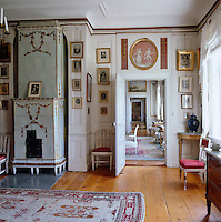 Gilt-framed portraits surround the doorway and walls of this drawing room which features a tiled stove decorated with gold hand-painted garlands