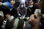 Medics tried to revive a man who had fainted from tear gas at the field hospital in Tahrir Square, Cairo, Egypt, Sunday, Nov. 20, 2011. Around 1500 people have been injured and 23 killed in the clashes ahead of Egypt's parliamentary election beginning on November 28.