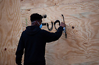 A demonstrator spray paints a building during a protest in Washington, D.C., U.S., on Monday, June 1, 2020, following the death of an unarmed black man at the hands of Minnesota police on May 25, 2020.  More than 200 active duty military police were deployed to Washington D.C. following three days of protests.  Credit: Stefani Reynolds / CNP/AdMedia
